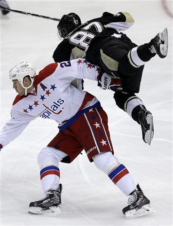 Pittsburgh Penguins center Sidney Crosby (87) is upended by Washington Capitals' Brooks Laich (21) during the first period of an NHL hockey game in Pittsburgh on Tuesday, March 19, 2013. (AP Photo/Gene J. Puskar)