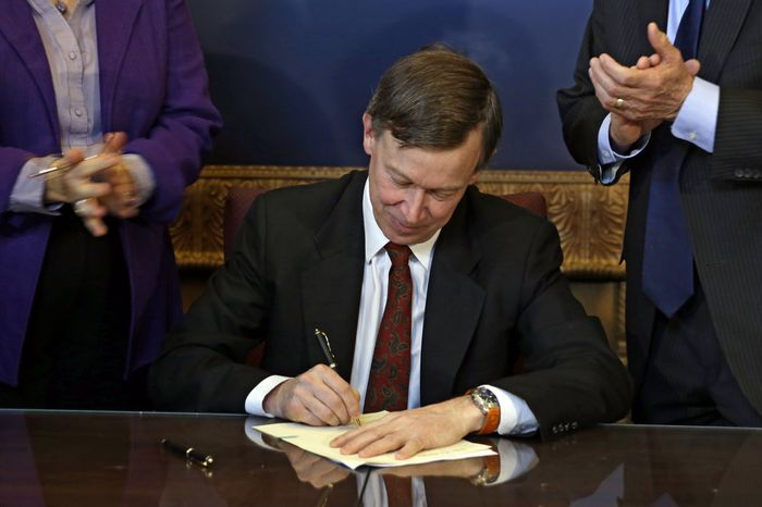** FILE ** Colorado Gov. John Hickenlooper is applauded by lawmakers as he signs the state's gun-control bill into law at the Capitol in Denver on Wednesday, March 20, 2013. (AP Photo/Ed Andrieski, Pool)