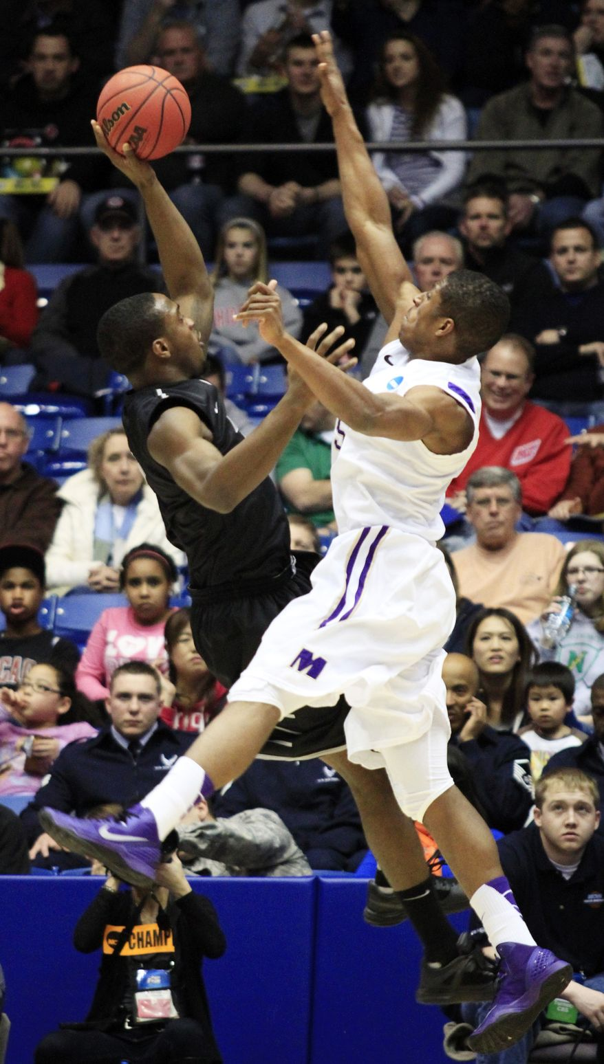 LIU Brooklyn's Gerrell Martin, left, shoots over James Madison guard Alioune Diouf in the first half of a first-round game of the NCAA college basketball tournament, Wednesday, March 20, 2013, in Dayton, Ohio. (AP Photo/Skip Peterson)