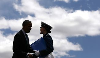 President Obama is silhouetted as he congratulates a graduate of the 2012 class of the U.S. Air Force Academy in Colorado Springs, Colo., on May 23, 2012. (Associated Press)