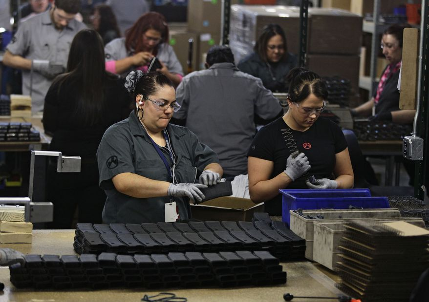 **FILE** Workers assemble 30-round capacity ammunition magazines for high-velocity rifles inside the Magpul Industries plant in Erie, Colo., on Feb. 28, 2013. (Associated Press)