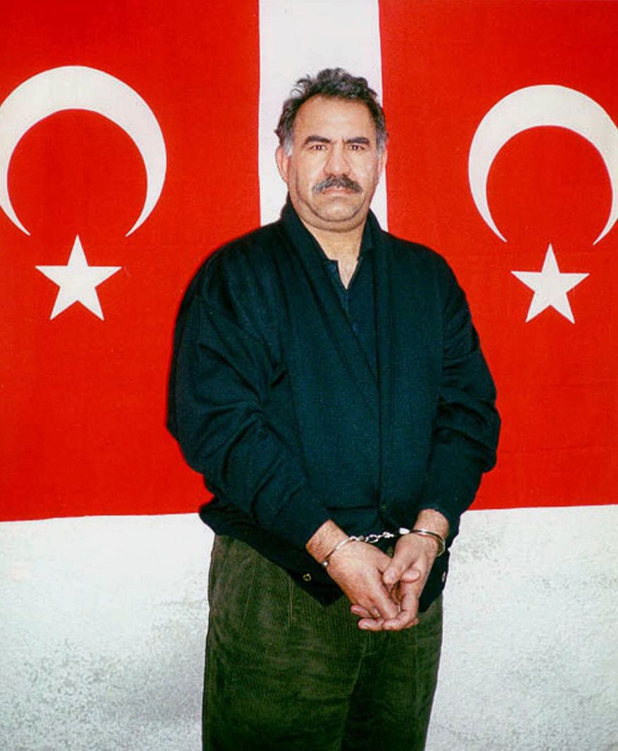 ** FILE ** In this file photo provided by the Turkish Intelligence Service on Feb. 18, 1999, Kurdish rebel leader Abdullah Ocalan poses in front of Turkish flags before being interrogated by Turkish officials at the prison-island of Imrali , Turkey. (AP Photo/Turkish Intelligence Service, File)