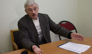 Oleg Orlov, a member of the Russian human rights group Memorial, talks to the media in his office in Moscow on Thursday, March 21, 2013, as prosecutors search for documents pertaining to all of the organization's activities. (AP Photo/Ivan Sekretarev)