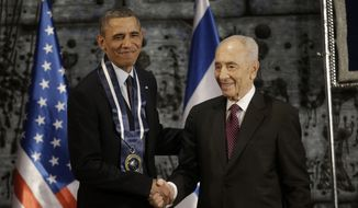 President Obama shakes hands with Israeli President Shimon Peres after Peres presented him the Israeli Medal of Distinction on March 21, 2013, at a State Dinner at President's residence in Jerusalem. (Associated Press)