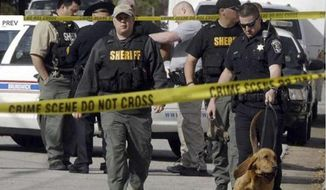 Authorities investigate the scene of shooting in Brunswick, Ga., on March 21, 2013. A young boy opened fire on a woman pushing her baby in a stroller in a Georgia neighborhood, killing the 1-year-old boy and wounding the mother, police said. (Associated Press/The Morning News) ** FILE **