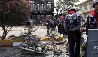 Myanmar police officers provide security near burnt buildings in Meikhtila, where ethnic unrest between Buddhists and Muslims continues, in Mandalay division, about 550 kilometers (340 miles) north of Yangon, Myanmar, Friday, March. 22, 2013. (AP Photo/Khin Maung Win)