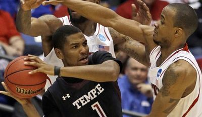 Temple guard Khalif Wyatt (1) is trapped by North Carolina State guard Lorenzo Brown, right, and forward Richard Howell in the second half of a second-round game at the NCAA college basketball tournament, Friday, March 22, 2013, in Dayton, Ohio. (AP Photo/Al Behrman)