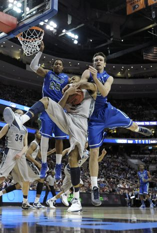 Georgetown's Otto Porter Jr., center, pulls in a rebound against Florida Gulf Coast's Sherwood Brown, left, and Eddie Murray during the first half of a second-round game of the NCAA college basketball tournament, Friday, March 22, 2013, in Philadelphia. (AP Photo/Michael Perez)