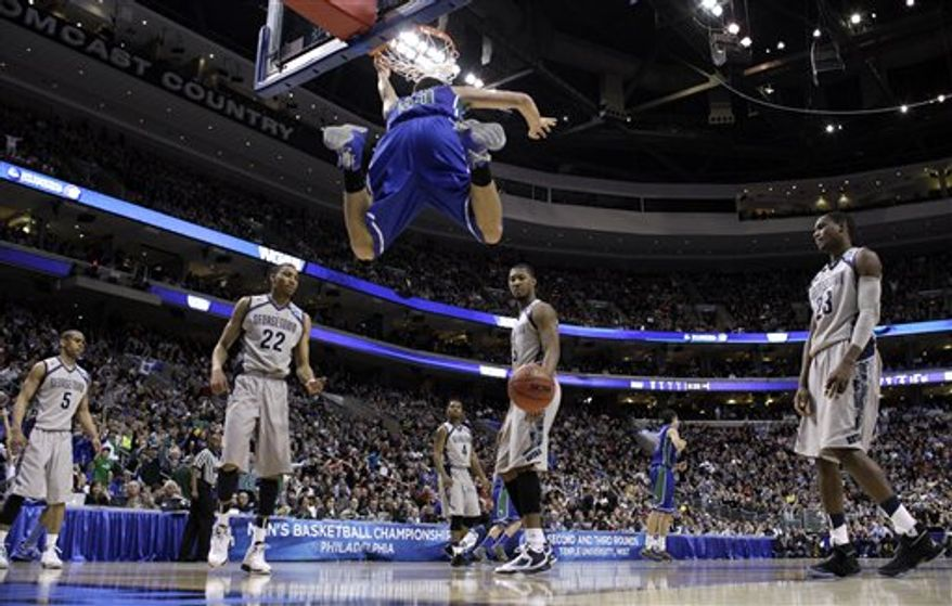 Florida Gulf Coast's Chase Fieler (20) hangs from the rim after a dunk as Georgetown's Markel Starks (5), Otto Porter Jr. (22), D'Vauntes Smith-Rivera (4), Mikael Hopkins (3) and Aaron Bowen (23) look on during the second half of a second-round game of the NCAA college basketball tournament on Friday, March 22, 2013, in Philadelphia. Florida Gulf Coast won 78-68. (AP Photo/Matt Rourke)