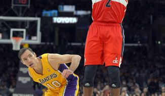 Washington Wizards guard John Wall, right, puts up a shot as Los Angeles Lakers guard Steve Nash defends during the second half of their NBA basketball game, Friday, March 22, 2013, in Los Angeles. The Wizards won 103-100. (AP Photo/Mark J. Terrill)