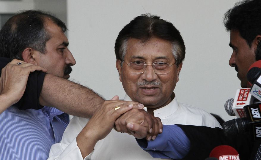 ** FILE ** Former Pakistani President Pervez Musharraf (center), surrounded by guards, arrives at the airport in Karachi, Pakistan, on Sunday, March 24, 2013, after more than four years in self-exile. Mr. Musharraf is seeking a possible political comeback in defiance of judicial probes and death threats from Taliban militants. (AP Photo/Shakil Adil)