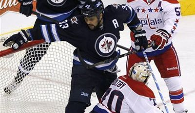 Winnipeg Jets' Nik Antropov (80) looks for the rebound as teammate Dustin Byfuglien (33) gets tangled with Washington Capitals goaltender Braden Holtby (70) and Capitals' Mike Green (52) during the third period of an NHL hockey game in Winnipeg, Manitoba, on Friday, March 22, 2013. (AP Photo/The Canadian Press, John Woods)