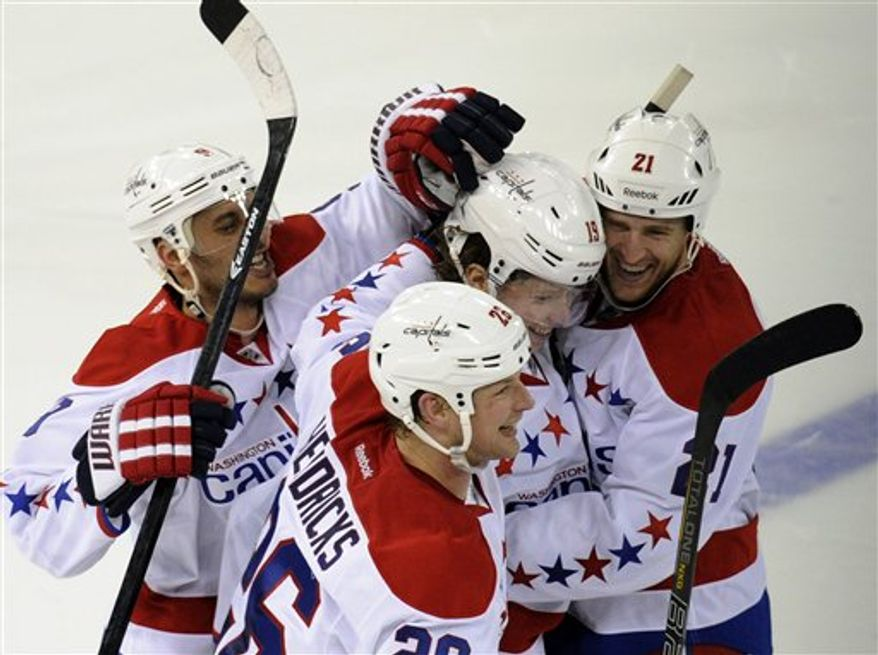 Washington Capitals' Nicklas Backstrom (19), left, of Sweden, celebrates with teammates Brooks Laich (21), Matt Hendricks (26), and Mike Ribeiro (9) after Backstrom scored during the shootout to defeat the New York Rangers, 3-2, in an NHL hockey game Sunday, March 24, 2013, at Madison Square Garden in New York. (AP Photo/Bill Kostroun)