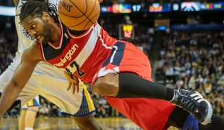 Washington Wizards' Nene drives to the basket against Golden State Warriors' Festus Ezeli in the first quarter of an NBA basketball game in Oakland, Calif., Saturday, March 23, 2013. (AP Photo/John Storey)