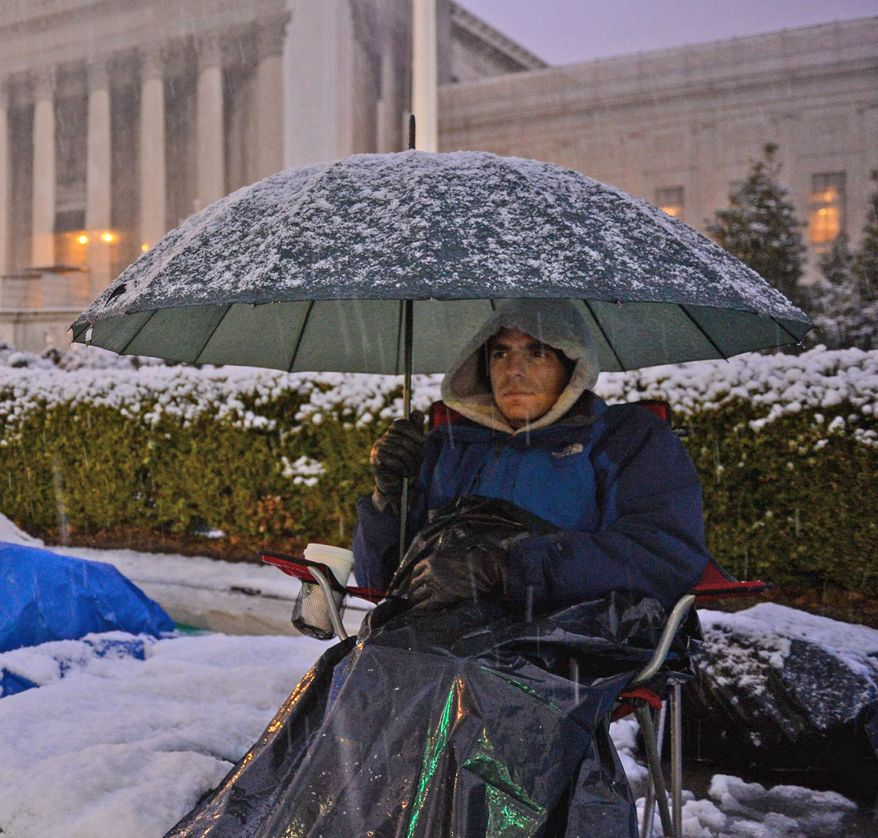 Jeffery DeSoto of New York City endures the snow Monday while camping out in front of the Supreme Court. Oral arguments on a pair of landmark gay-marriage cases begin Tuesday. (Andrew Harnik/The Washington Times)