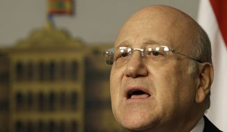 Lebanese Prime Minister Najib Mikati announces his resignation at the government palace in Beirut on Friday, March 22, 2013. (AP Photo/Hussein Malla)