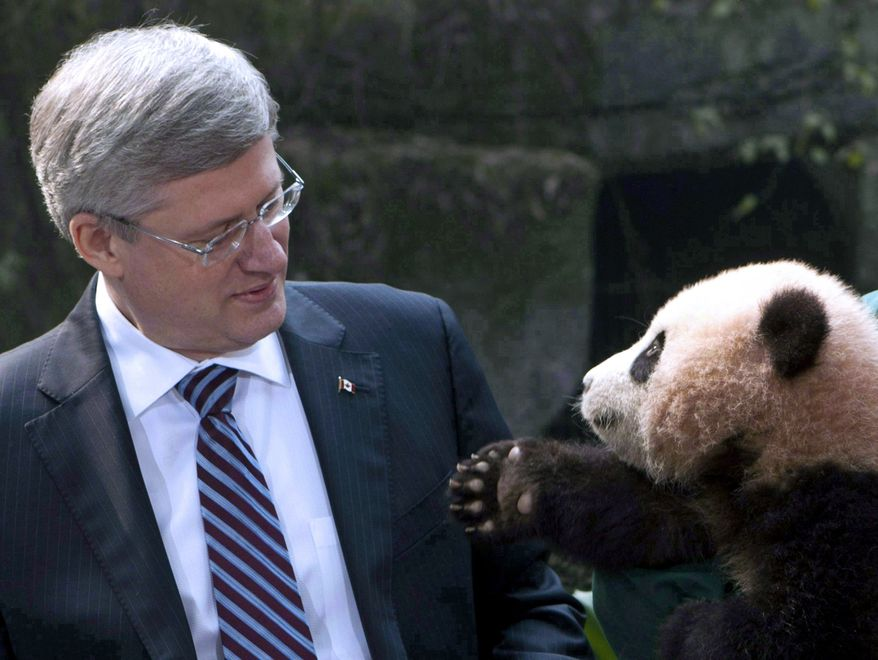 ** FILE ** In this Feb. 11, 2012, photo, panda reaches for Prime Minister Stephen Harper at the Chongqing Zoo in Chongqing, China. (AP Photo/The Canadian Press, Adrian Wyld)