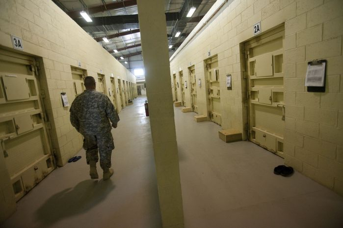 ** FILE ** This Sept. 27, 2010, file photo reviewed by the U.S. military, shows a U.S. military guard walking a corridor between detainee cells at the Parwan detention facility near Bagram, north of Kabul, Afghanistan. (AP Photo/David Guttenfelder, File)