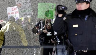 ** FILE ** Protesters hold signs for immigrant rights outside of Kluczynski Federal Building in downtown Chicago, Friday, March 22, 2013. (AP Photo/Nam Y. Huh)