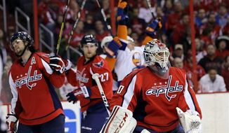 Washington Capitals goalie Braden Holtby (70) stands near defensemen Mike Green, left, and Karl Alzner after the go-ahead goal by New York Islanders center John Tavares, behind, in the third period of an NHL hockey game Tuesday, March 26, 2013 in Washington. The Islanders won 3-2. (AP Photo/Alex Brandon)