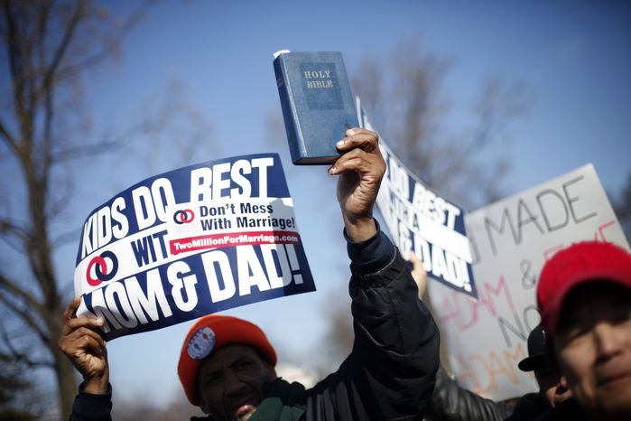A demonstrator holds a bible while marching outside the Supreme Court in Washington, Tuesday, March 26, 2013, as the court heard arguments on California's voter approved ban on same-sex marriage, Proposition 8. (AP Photo/Pablo Martinez Monsivais)