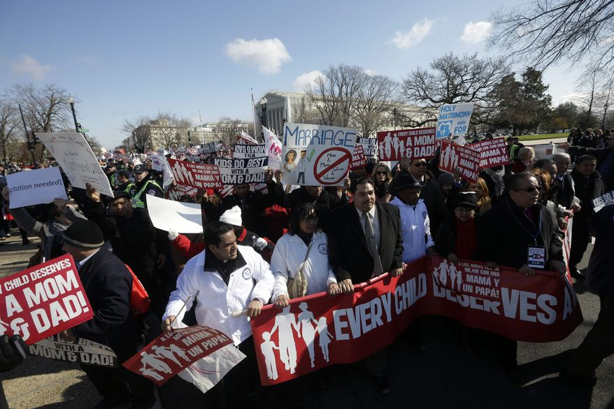 Demonstrators march outside the Supreme Court in Washington, Tuesday, March 26, 2013, where the justices were hearing arguments on California's voter approved ban on same-sex marriage, Proposition 8. (AP Photo/Pablo Martinez Monsivais)