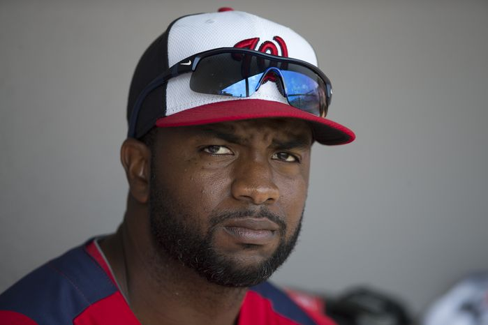 Washington Nationals outfielder Denard Span sits in the dugout before the start of an exhibition spring training baseball game against the Atlanta Braves on Sunday, March 24, 2013, in Viera, Fla. (AP Photo/Evan Vucci)