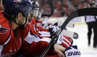 Washington Capitals center Brooks Laich (21), left, and others rest on the bench during a timeout in the first period of an NHL hockey game against the New York Islanders Tuesday, March 26, 2013 in Washington. (AP Photo/Alex Brandon)