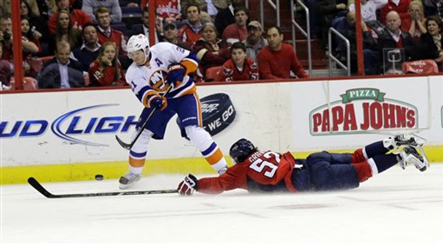 Washington Capitals defenseman Mike Green (52) dives to prevent an empty-net goal by New York Islanders right wing Kyle Okposo late in the third period of an NHL hockey game Tuesday, March 26, 2013 in Washington. The Islanders won 3-2. (AP Photo/Alex Brandon)