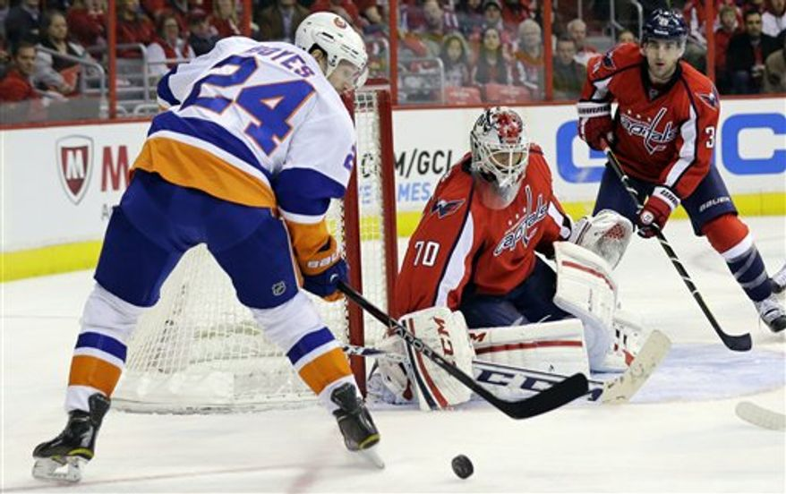 New York Islanders center Brad Boyes (24) tries to get the bouncing puck past Washington Capitals goalie Braden Holtby (70) in the third period of an NHL hockey game Tuesday, March 26, 2013 in Washington. The Islanders won 3-2. (AP Photo/Alex Brandon)