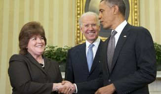 **FILE** President Obama shakes hands with the new director of the U.S. Secret Service Director Julia Pierson after she was sworn in by Vice President Joseph R. Biden in the Oval Office of the White House in Washington on March 27, 2013. Pierson is the first female director in the agency's 148-year history. (Associated Press)