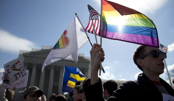 Kevin Coyne of Washington holds flags in front of the Supreme Court in Washington on March 27, 2013. The U.S. Supreme Court, in the second day of gay marriage cases, turned to a constitutional challenge to the federal law that prevents legally married gay Americans from collecting federal benefits generally available to straight married couples. (Associated Press)