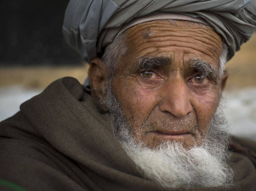 Afghan villager Ghulam Rasool sits in the yard of the house where he and his family found refuge in Khalis Family Village, Nangarhar province, Afghanistan, on Wednesday, March 20, 2013. (AP Photo/Anja Niedringhaus)