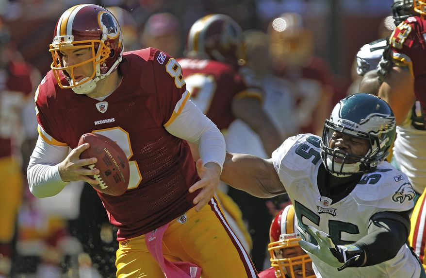 Washington Redskins quarterback Rex Grossman, left, scrambles out of the reach of Philadelphia Eagles defensive end Darryl Tapp during the first half of an NFL football game in Landover, Md., Sunday, Oct. 16, 2011. (AP Photo/Pablo Martinez Monsivais)