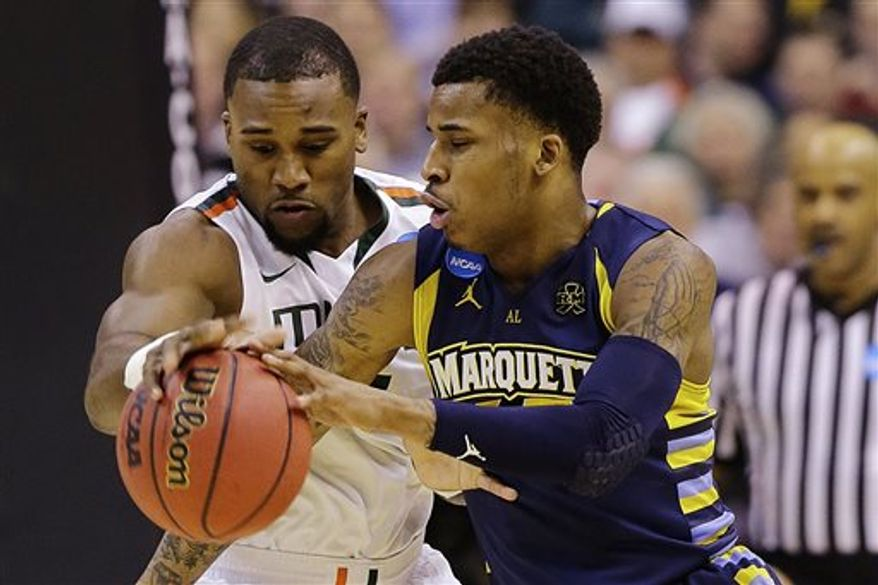 Marquette guard Vander Blue, right, drives around Miami forward Erik Swoope during the first half of an East Regional semifinal in the NCAA college basketball tournament, Thursday, March 28, 2013, in Washington. (AP Photo/Alex Brandon)
