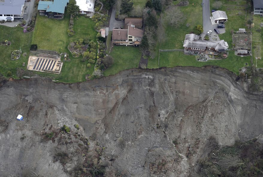 In this aerial photo, houses sit near the edge of a landslide, near Coupeville, Wash. on Whidbey Island, Wednesday, March 27, 2013. (AP Photo/Ted S. Warren)