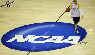 Marquette guard Jake Thomas moves over the NCAA logo during practice for a regional semifinal game in the NCAA college basketball tournament, Wednesday, March 27, 2013, in Washington. Marquette plays Miami on Thursday. (AP Photo/Pablo Martinez Monsivais)