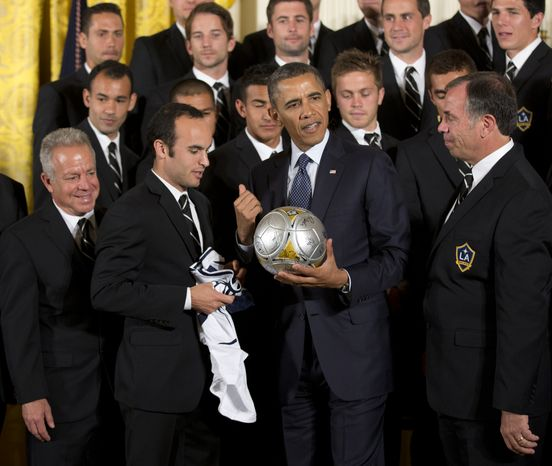 President Barack Obama, center is presented with the LA Galaxy team jersey by captain Landon Donovan, left, and head coach Bruce Arena, right, during a ceremony in the East Room of the White House in Washington, Tuesday, March 26, 2013, honoring the Stanley Cup hockey champion Los Angeles Kings and the Major League Soccer champion LA Galaxy. (AP Photo/Manuel Balce Ceneta)