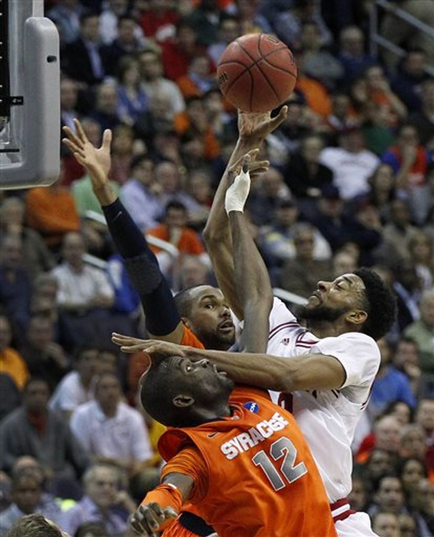 Indiana forward Christian Watford (2) shoots over Syracuse center Baye Keita (12) during the second half of a East Regional semifinal in the NCAA college basketball tournament, Thursday, March 28, 2013 in Washington. Syracuse defeated Indiana 61-50. (AP Photo/Alex Brandon)