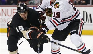 Anaheim Ducks' Ryan Getzlaf, left, and Chicago Blackhawks' Jonathan Toews vie for the puck during the second period of an NHL hockey game in Anaheim, Calif., Wednesday, March 20, 2013. (AP Photo/Jae C. Hong)