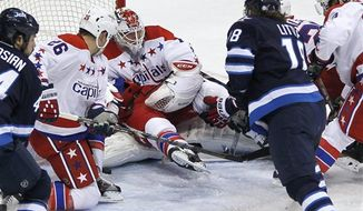 Washington Capitals goaltender Braden Holtby (70) saves a Winnipeg Jets shot despite teammate Mike Green landing on him during the third period of an NHL hockey game in Winnipeg, Manitoba, on Thursday, March 21, 2013. The Capitals won 4-0. (AP Photo/The Canadian Press, John Woods)