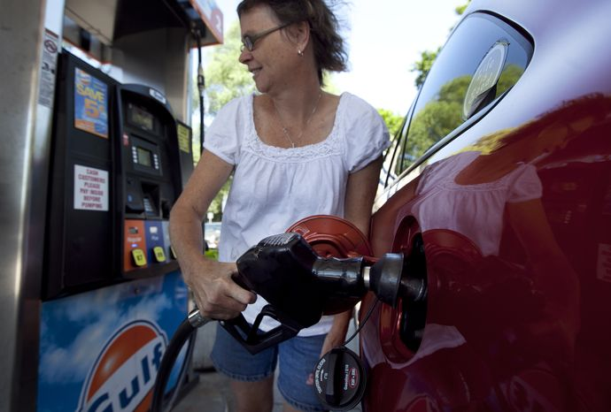 **FILE** Suzanne Meredith, of Walpole, Mass., gases up her car at a Gulf station in Brookline, Mass., on July 10, 2012. (Associated Press)