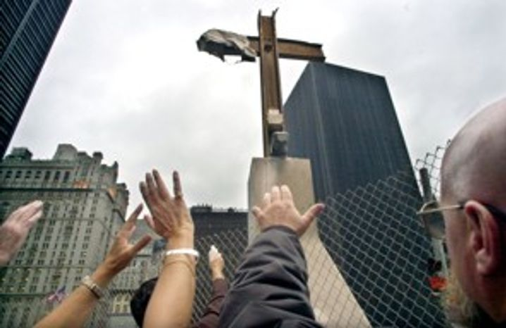 ** FILE ** Hands stretch towards what has become known as the Ground Zero Cross at the World Trade Center site in New York, Oct. 3, 2002. (Associated Press)