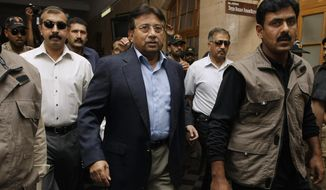 ** FILE ** Former Pakistani President Pervez Musharraf, center, surrounded by guards arrives in a court in Karachi, Pakistan on Friday, March 29, 2013. (AP Photo/Fareed Khan)