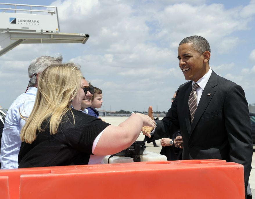President Barack Obama greets people after arriving on Air Force One at Miami International Airport in Miami, Friday, March 29, 2013. Obama is promoting a plan to create jobs by attracting private investment in highways and other public works during a visit to a Miami port on Friday (AP Photo/Susan Walsh)