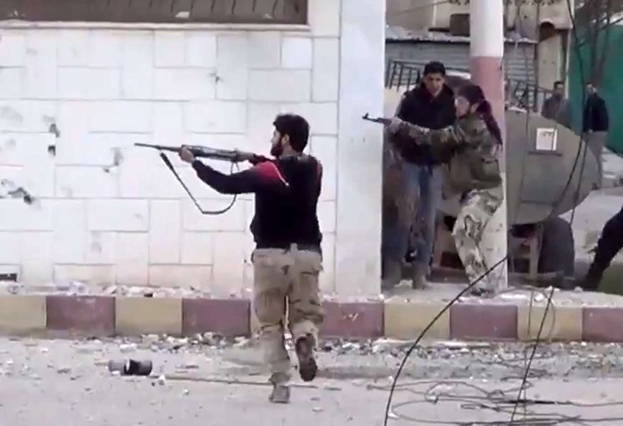 ** FILE ** In this image taken from video obtained from the Shaam News Network, which has been authenticated based on its contents and other AP reporting, Free Syrian Army fighters fire at Syrian army soldiers during a fierce firefight in Daraa al-Balad, Syria, Monday, March 18, 2013. (AP Photo/Shaam News Network via AP video)