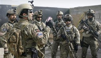 ** FILE **  - A member of the Afghan special forces, left, briefs soldiers after a training exercise on the outskirts of Kabul, Afghanistan, Jan. 14, 2013. A senior U.S. commander said Saturday, March 30, 2013 that American special operations forces have handed over their base in eastern Afghanistan's Nirkh district to local Afghan commandos. (Associated Press)