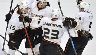 Anaheim Ducks' Sheldon Souray, second from left, celebrates with teammates Ryan Getzlaf, left, Francois Beauchemin, second from right, and Bobby Ryan, right, after scoring against the Chicago Blackhawks during the third period of an NHL hockey game in Chicago, Friday, March, 29, 2013. Anaheim won 2-1. (AP Photo/Paul Beaty)