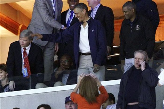 President Barack Obama waves to the crowd as he watches the first half of the East Regional final in the NCAA men's college basketball tournament between Syracuse and Marquette, Saturday, March 30, 2013, in Washington. (AP Photo/Mark Tenally)