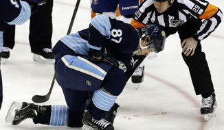 Pittsburgh Penguins center Sidney Crosby (87) is helped by referee Ian Walsh (29) after being hit in the face with a puck during the first period of an NHL hockey game against the New York Islanders in Pittsburgh, Saturday, March 30, 2013. Crosby left the game. (AP Photo/Gene J. Puskar)